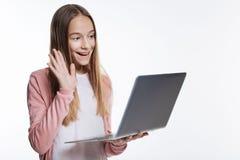 Adolescente agradable que hace una llamada video vía el ordenador portátil Fotografía de archivo