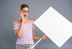 Adolescente agradable que lleva a cabo una bandera y un grito Foto de archivo