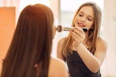Adolescente agradable que practica en la aplicación de maquillaje Imágenes de archivo libres de regalías