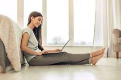 Adolescente agradable que se sienta en piso y que usa el ordenador portátil Fotos de archivo