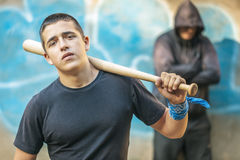Adolescente agresivo con un bate de béisbol en fondo del edificio Fotos de archivo libres de regalías