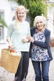 Adolescente aidant la femme supérieure à Carry Shopping Photographie stock libre de droits