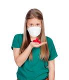 Adolescente alérgico con la mascarilla que mira los pétalos rojos Imagen de archivo