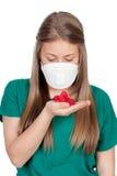 Adolescente alérgico con la mascarilla que mira los pétalos rojos Fotos de archivo