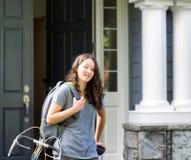 Adolescente al aire libre con el bolso de escuela y la bicicleta delante de ho Imágenes de archivo libres de regalías