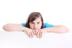 Adolescente al lado de un espacio en blanco blanco. Foto de archivo libre de regalías