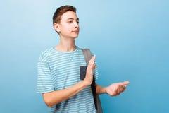Adolescente alegre com mãos de aplauso, em um fundo azul fotos de stock royalty free