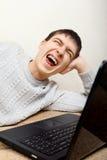 Adolescente alegre con el ordenador portátil Foto de archivo