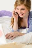Adolescente alegre con el teléfono y el ordenador portátil Fotografía de archivo libre de regalías