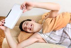Adolescente alegre con la tableta Imagen de archivo libre de regalías