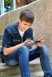 Adolescente alegre con la tableta Foto de archivo