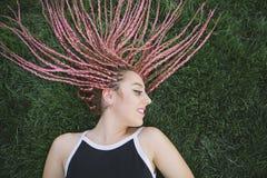 Adolescente alegre con las trenzas rosadas en la hierba Imagen de archivo libre de regalías