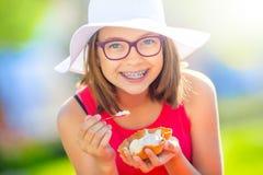 Adolescente alegre con los vidrios de los apoyos y el helado dentales Retrato de una chica joven bonita sonriente en equipo del v Fotografía de archivo