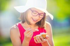 Adolescente alegre con los vidrios de los apoyos y el helado dentales Retrato de una chica joven bonita sonriente en equipo del v Imagen de archivo libre de regalías