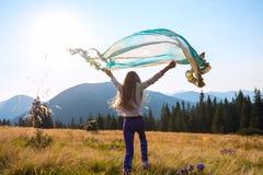 Adolescente alegre con una bufanda que agita en sus manos Fotografía de archivo