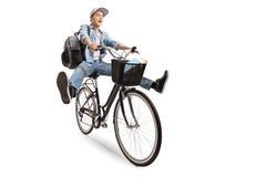 Adolescente alegre con una mochila que monta una bicicleta Foto de archivo