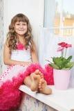 Adolescente alegre de la muchacha que se sienta en windowsil en sitio Imagen de archivo libre de regalías