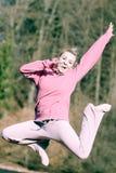 Adolescente alegre de la mujer en el salto rosado del chándal al aire libre Fotografía de archivo libre de regalías