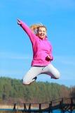 Adolescente alegre de la mujer en mostrar de salto del chándal al aire libre Imagen de archivo libre de regalías