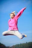 Adolescente alegre de la mujer en mostrar de salto del chándal al aire libre Fotos de archivo libres de regalías