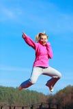 Adolescente alegre de la mujer en mostrar de salto del chándal al aire libre Foto de archivo libre de regalías