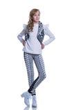 Adolescente alegre dulce que lleva el chaleco hecho punto, los pantalones y las botas modernas aislados en el fondo blanco Ropa d Fotos de archivo