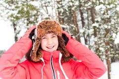 Adolescente alegre en el earflap caliente que se divierte en delanteras del invierno Foto de archivo libre de regalías