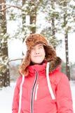 Adolescente alegre en el earflap caliente que se divierte en delanteras del invierno Imagen de archivo