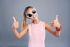 Adolescente alegre en las gafas de sol frescas que muestran los pulgares-para arriba Imágenes de archivo libres de regalías