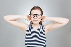 Adolescente alegre en los vidrios que se colocan con las manos detrás de la cabeza Imagen de archivo libre de regalías