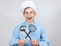Adolescente alegre joven con la cucharón y humor en el sombrero de un cocinero En el fondo blanco, estudio Imágenes de archivo libres de regalías