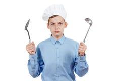 Adolescente alegre joven con la cucharón y humor en el sombrero de un cocinero Estudio aislado Imagenes de archivo