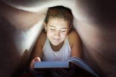 Adolescente alegre joven que oculta debajo de la manta y que lee abucheo Imagenes de archivo
