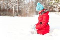 Adolescente alegre joven que se sienta en la nieve acumulada por la ventisca que disfruta de invierno Imágenes de archivo libres de regalías