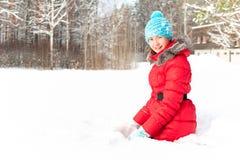 Adolescente alegre joven que se sienta en la nieve acumulada por la ventisca que disfruta de invierno Fotos de archivo