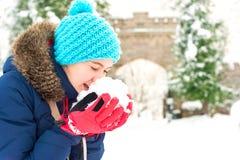 Adolescente alegre joven que sostiene el montón de la nieve suave Foto de archivo