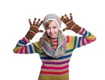Adolescente alegre lindo que lleva el suéter, la bufanda, guantes coloridos y el sombrero rayados aislados en el fondo blanco Rop Foto de archivo libre de regalías