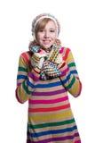 Adolescente alegre lindo que lleva el suéter, la bufanda, guantes coloridos y el sombrero rayados aislados en el fondo blanco Rop Imagen de archivo