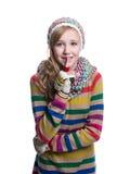 Adolescente alegre lindo que lleva el suéter, la bufanda, guantes coloridos y el sombrero rayados aislados en el fondo blanco Rop Foto de archivo