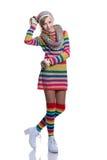 Adolescente alegre lindo que lleva el suéter rayado colorido, la bufanda, los guantes, el sombrero y las botas blancas aislados R Fotografía de archivo