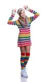 Adolescente alegre lindo que lleva el suéter rayado colorido, la bufanda, los guantes, el sombrero y las botas blancas aislados R Imagenes de archivo