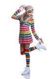 Adolescente alegre lindo que lleva el suéter rayado colorido, la bufanda, los guantes, el sombrero y las botas blancas aislados R Foto de archivo
