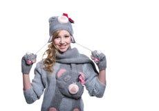 Adolescente alegre precioso que lleva el suéter, la bufanda, las manoplas borrosas y el sombrero aislados en el fondo blanco Ropa Fotos de archivo libres de regalías
