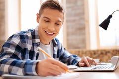 Adolescente alegre que aprende sus lecciones en casa Imagenes de archivo