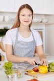 Adolescente alegre que cocina la cena sana en la cocina Imágenes de archivo libres de regalías