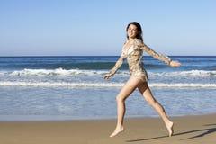 Adolescente alegre que corre a través de la playa Imagenes de archivo