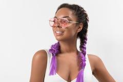 Adolescente alegre que demuestra sus coletas violetas del kanekalon Fotos de archivo