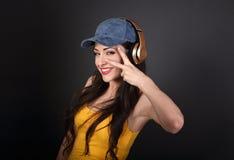 Adolescente alegre que escucha la música en el auricular inalámbrico a del oro Foto de archivo