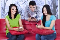 Adolescente alegre que manda un SMS con el teléfono móvil Imagen de archivo
