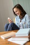 Adolescente alegre que mira el hogar del teléfono móvil Fotografía de archivo